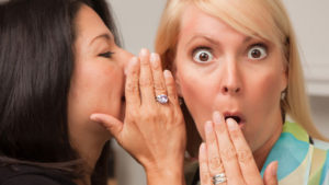 A lady is telling secrets and the other lady is surprised by the secret.